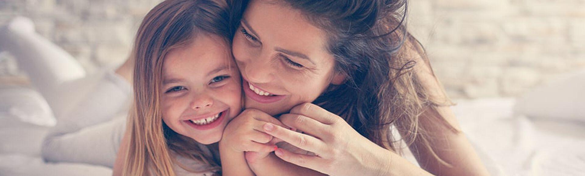 Madre e hija abrazadas en la cama